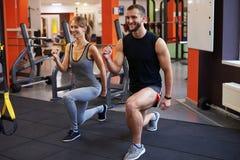 Femme d'athlète avec l'entraîneur personnel faisant des postures accroupies au gymnase photos libres de droits