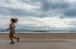 Femme d'Atlethic courant devant la plage photographie stock libre de droits