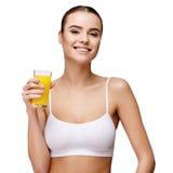 Femme d'Attractivesmiling jugeant le verre de jus d'orange d'isolement sur le blanc Photos stock