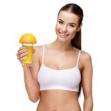 Femme d'Attractivesmiling jugeant le verre de jus d'orange d'isolement sur le blanc Photo stock