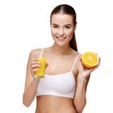 Femme d'Attractivesmiling jugeant le verre de jus d'orange d'isolement sur le blanc Image stock