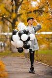 Femme d'automne en parc d'automne avec des ballons Fille de mode dans le manteau gris photographie stock libre de droits