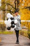 Femme d'automne en parc d'automne avec des ballons Fille de mode dans le manteau gris photos stock