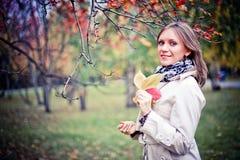Femme d'automne heureuse en parc de chute regardant autour de avoir l'amusement souriant dans le beau feuillage coloré de forêt Photographie stock