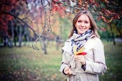 Femme d'automne heureuse en parc de chute regardant autour de avoir l'amusement souriant dans le beau feuillage coloré de forêt Photos stock