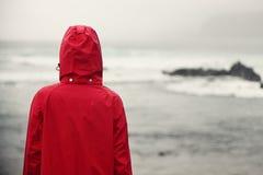 Femme d'automne sous la pluie regardant l'océan Photos stock