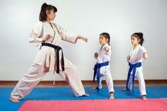 Femme d'entraîneur montrant l'art martial pour des enfants photo stock