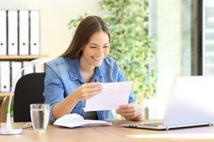 Femme d'entrepreneur lisant une lettre au bureau photographie stock libre de droits