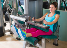 Femme d'exercice de machine assise par gymnase de boucle de jambe photos stock