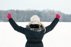 Femme d'hiver la représentation de neige sa de retour et en faisant face à la forêt Photographie stock libre de droits