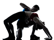 Femme d'homme d'entraîneur exerçant la position de passerelle de yoga Photographie stock