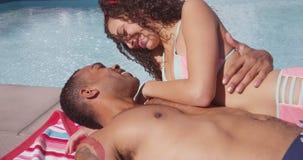 Femme d'homme de couleur et d'hispanique embrassant par la piscine dans l'amour Photo libre de droits