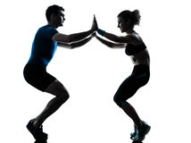 Femme d'homme exerçant la forme physique de séance d'entraînement de postures accroupies photographie stock
