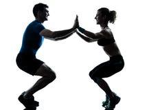 Femme d'homme exerçant la forme physique de séance d'entraînement de squatts Photo stock
