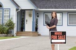 Femme d'immobiliers debout en dehors d'une maison à vendre Image libre de droits