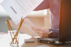Femme d'indépendant lisant un contrat se reposant à la table Photos stock