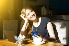 Femme d'indépendant travaillant en ligne sur l'ordinateur portable et le téléphone portable tout en se reposant en café photo stock