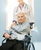 Femme d'infirmière avec l'aîné dans le fauteuil roulant Images libres de droits