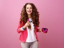 Femme d'isolement sur le rose montrant les bonbons au chocolat en forme de coeur Photos libres de droits