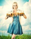Femme d'Oktoberfest avec six tasses de bière Photographie stock libre de droits