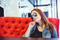 Femme d'Oung avec des verres sur un sofa rouge dans un café de rue Photo libre de droits