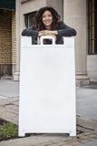 Femme d'une chevelure assez bouclée avec le panneau publicitaire porté par un homme-sandwich Photos stock