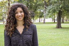 Femme d'une chevelure assez bouclée dans le sourire de parc Photographie stock