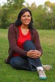 Femme d'une chevelure assez foncée sur l'herbe Image libre de droits