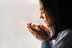 Femme d'une chevelure foncée de Yound tenant le verre de tisane fraîche Photo stock