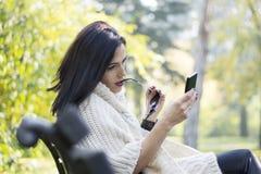Femme d'une chevelure noire attirante à l'aide du téléphone Image stock