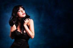Femme d'une chevelure noire attirante dans une robe noire Photos stock