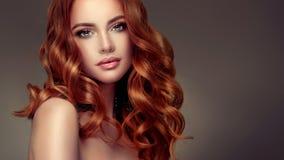Femme d'une chevelure rouge avec la coiffure volumineuse, brillante et bouclée Cheveu de vol image libre de droits