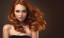 Femme d'une chevelure rouge avec la coiffure volumineuse, brillante et bouclée Cheveu de vol photographie stock