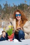 Femme d'une chevelure rouge avec plaisir s'asseyant en congère contre l'environnement rural photographie stock