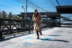 Femme d'une cinquantaine d'années élégamment habillée jouant le jeu de marelle, ayant l'amusement en tant qu'enfant, sautant et s images libres de droits