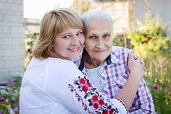Femme d'une cinquantaine d'années étreignant sa mère en nature La vraie émotion Photographie stock libre de droits