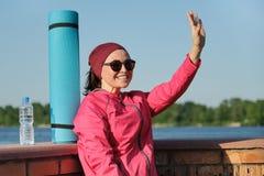 Femme d'une cinquantaine d'années de sports avec le tapis de yoga et la bouteille de l'eau photo stock