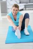 Femme d'une cinquantaine d'années étirant ses jambes Image stock