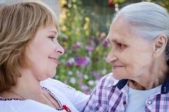 Femme d'une cinquantaine d'années étreignant sa mère en nature La vraie émotion Images libres de droits