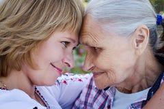 Femme d'une cinquantaine d'années étreignant sa mère en nature La vraie émotion Photographie stock