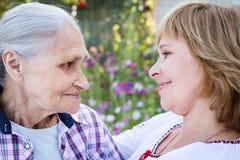 Femme d'une cinquantaine d'années étreignant sa mère en nature Les vraies émotions du bonheur la fleur de jour donne à des mères  Images stock