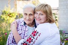 Femme d'une cinquantaine d'années étreignant sa mère en nature Les vraies émotions du bonheur la fleur de jour donne à des mères  Image libre de droits