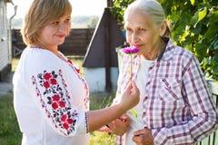 Femme d'une cinquantaine d'années étreignant sa mère en nature Les vraies émotions du bonheur la fleur de jour donne à des mères  Photo stock
