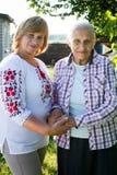 Femme d'une cinquantaine d'années étreignant sa mère en nature Les vraies émotions du bonheur la fleur de jour donne à des mères  Photo libre de droits