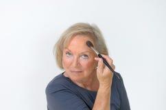 Femme d'une cinquantaine d'années attirante appliquant le maquillage Images stock