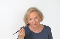 Femme d'une cinquantaine d'années attirante appliquant le maquillage Photographie stock libre de droits