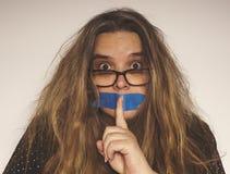 Femme d'une cinquantaine d'années avec la bouche attachée du ruban adhésif Photographie stock libre de droits