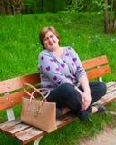 Femme d'une cinquantaine d'années détendant sur un banc de parc Images stock