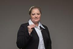 Femme d'une cinquantaine d'années d'affaires avec des verres dans le costume noir Image libre de droits