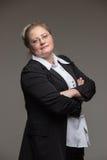 Femme d'une cinquantaine d'années d'affaires avec des verres dans le costume noir Photographie stock libre de droits